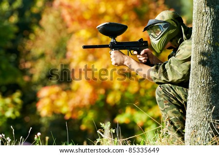 paintball sport player in protective uniform and mask aiming and shooting with gun outdoors - stock photo