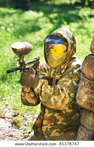 paintball sport player wearing protective mask aiming gun with head shot by paint spot