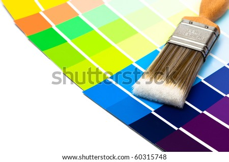Paintbrush with colour swatch cards on white background