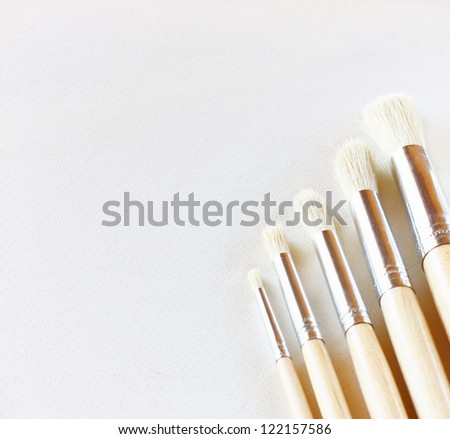 paintbrushes and empty canvas with texture