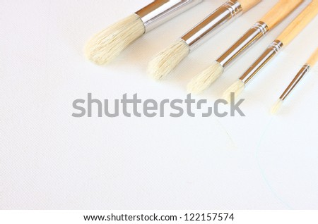 paintbrushes on empty canvas with texture