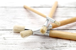 Paintbrushes on white grunge wooden table
