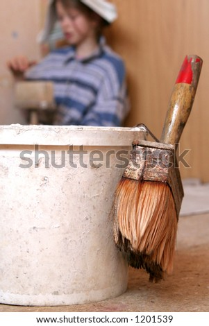 Paintbucket and paintbrush against a background of a little girl
