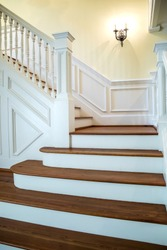 painted and natural stained wood stairs. Classic and tradition design with ornate banister