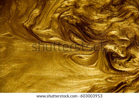 Painted background. Abstract emotional art. Modern design element. Golden liquid acrylic paints #603003953