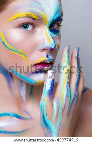 Painted beautiful woman face, artistic make up face art, close up. beauty fashion style in red, yellow, blue colors. - Shutterstock ID 459774919