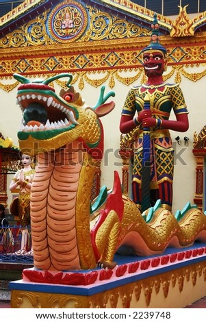Painted dragon statue standing beside a model of Buddha, outside Wat Chayamangkalaram, a Thai temple in Georgetown, on the Malaysian island on Penang.