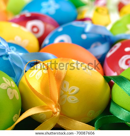 Painted easter eggs with bows over green background