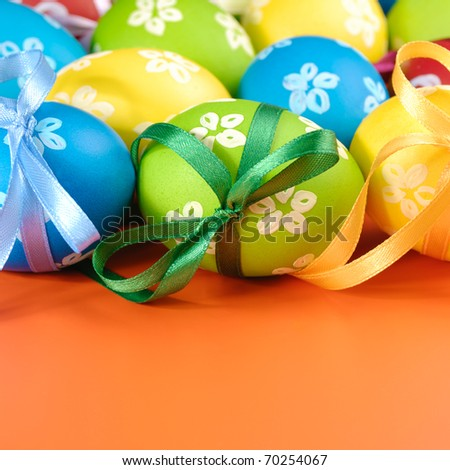 Painted easter eggs with bows over orange background
