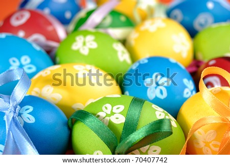Painted easter eggs with bows uniform background