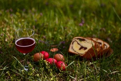 painted eggs for the Orthodox Easter celebration. romantic picnic with a glass of red wine and traditional Romanian products in the green glade near the forest