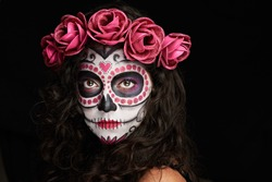 painted face for halloween as skull on woman isolated on black