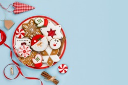 Painted gingerbread cookies and Christmas decoration isolated on blue background