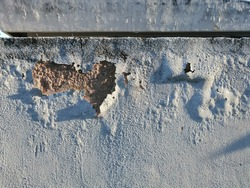 Painted grey colour peeling from concrete wall outdoor because of rain and humid. Hard shadow.