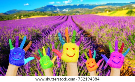 Painted hands with smiling faces against the backdrop of a field of lavender and mountains. The concept of summer vacations and travel. Family holidays, have fun together. Smile, laughter, diversity. #752194384