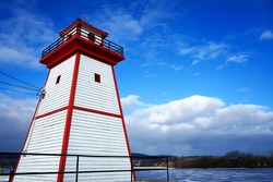 Painted in red and white lighthouse by the river, winter, Grenville, Canada