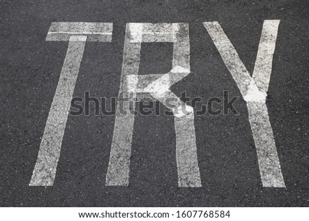 Painted lines on the asphalt road with the word TRY, perseverance and persistence message