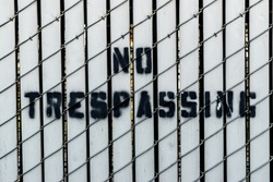 Painted no trespassing sign on wood and metal fence in urban area with room for copy text