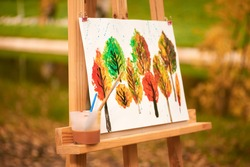 painted picture autumn with paints on canvas. an easel for drawing stands in the park