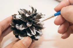 Painted pine cone. Decorated christmas cones. Handcraft. Made of natural materials. Process of creating.