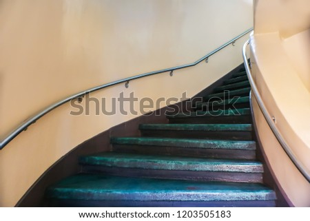 Painted purple curving concrete stairs with stuco walls disappearing around the curve #1203505183