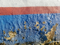Painted red and blue colour peeling from concrete wall outdoor because of rain and humid. Hard shadow.
