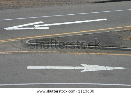 Painted road arrows pointing in the opposite direction.