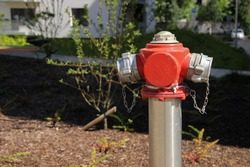 Painted steel hydrant stands at the lawn of a multistorey apartment. Fire hydrant at the public place.