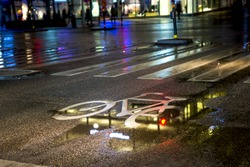 painted symbol in bicycle lane on wet street