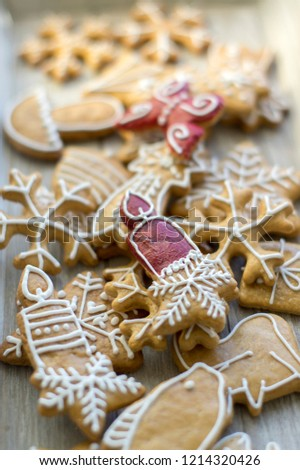 Painted traditional Christmas gingerbreads arranged on wooden tray in daylight, common tasty sweets for holidays, various shapes, snowflakes, candles and stars, white sugar icing painting