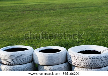 Painted white old tires on kart race course over green grass background #645166201