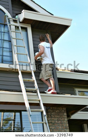 Painter at work on the exterior of a house.