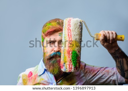 Painter. Bearded painter with paint roller in front of face. Painter with painting roller covered his face. Room painting job. Repair. Man worker. Construction. Industrial concept. Repair paintng tool