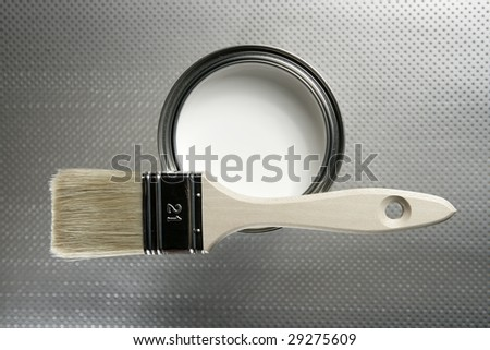 Painter brush and white paint tin macro over silver pattern background