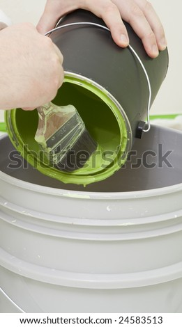 painter brushing in the paint in a bucket