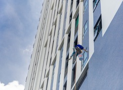Painter coming down the facade of a building tower rappelling with a rope