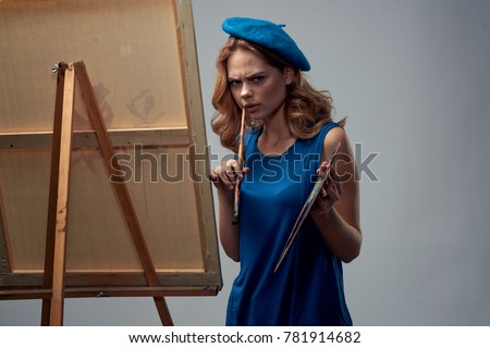 painter draws on a gray background, draw, art, drawing, paint, easel with a canvas #781914682