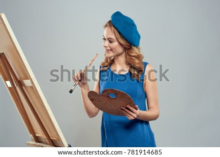 painter draws on a gray background, draw, art, drawing, paint, easel with a canvas #781914685