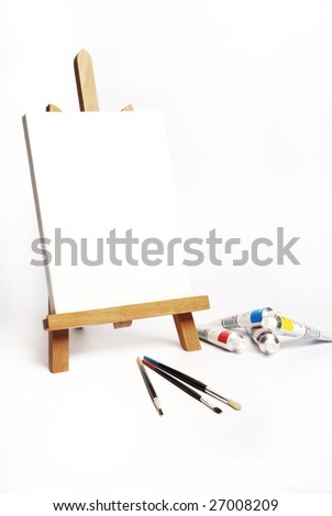 painter easel, brushes and acrylic colors on a white background