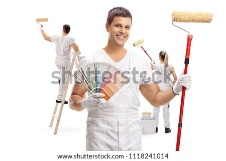 Painter holding a color swatch and a paint roller with two painters painting behind him isolated on white background