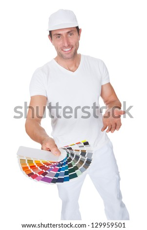 Painter Holding A Paint Roller And Spectrum Of Colour Samples On White Background