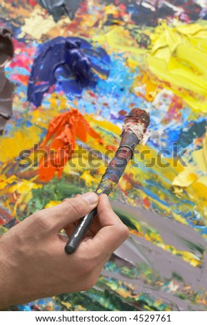 painter holding an over used brush against his abstract work