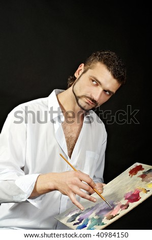 painter in a white shirt on a black background with a brush