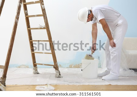 painter man at work with a paint roller and ladder, hand close up