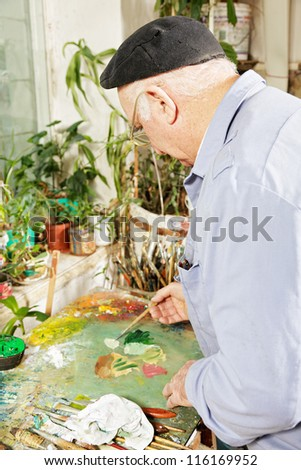 Painter mixing paints on palette sideview