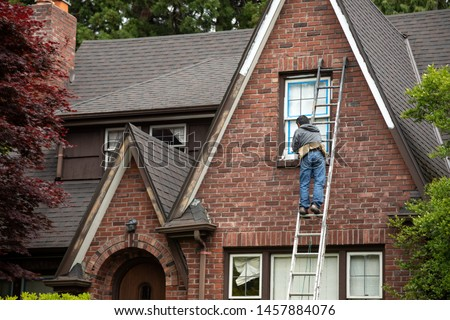 Painter on a ladder painting the windowsill of a brick house, in a home repair scene with space for text on the left