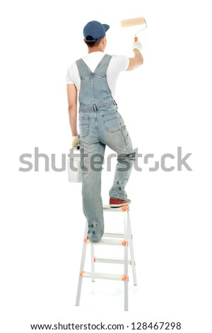 painter on the ladder painting the wall isolated on white background - stock photo