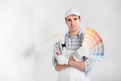 Painter or decorator with handful of colorful paint swatches or color cards holding a roller in his other hand as he smiles at the camera against a white wall