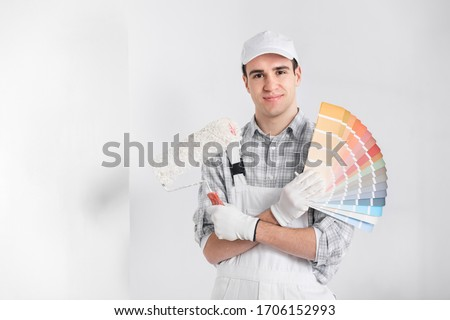 Painter or decorator with handful of colorful paint swatches or color cards holding a roller in his other hand as he smiles at the camera against a white wall Stockfoto ©