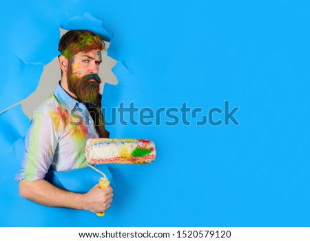 Painter. Painter with painting roller through hole in paper. Handsome bearded worker with paint roller. Professional painter in dirty shirt making hole in paper wall. Serious painter man. Copy space.